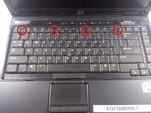 Locate and remove the four retaining clips from the edge of the keyboard. To remove pry up gently on the outside edge of the plastic clip. Once the clip pops up pull it straight out.