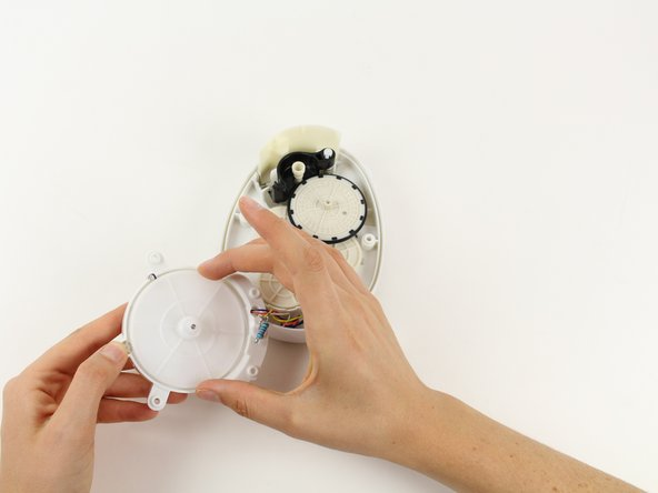 Grab the outside of the large, white gear in the LED housing and pull the gear out of the housing.