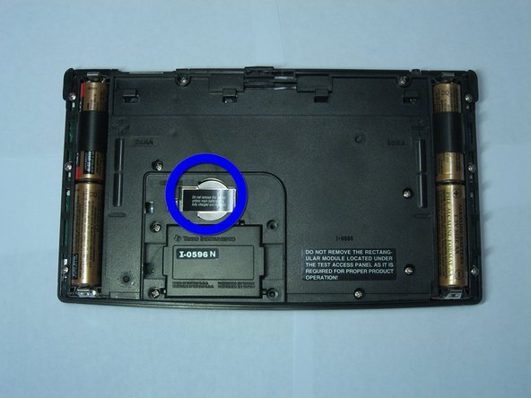 The backup battery can now be seen underneath a small metal cover held by a screw.