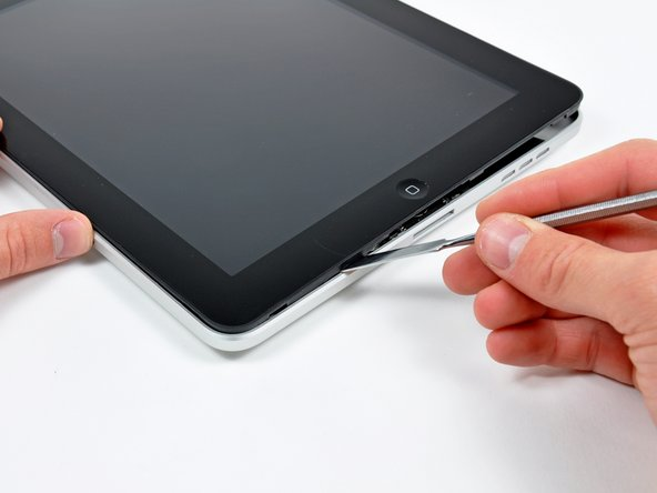 Image 1/2: Use extreme caution as you approach the top edge of the iPad. The digitizer ribbon cable is located near the edge of the rear panel and can easily be damaged.