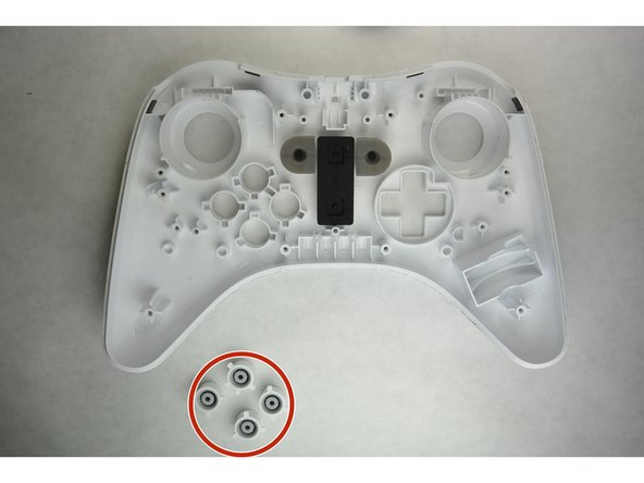 Once these two screws have been removed, you may go ahead and remove the board from with the controller by hand.  Set it to the side and direct your attention to the front panel of the controller.  Remove the buttons and wipe them down completely with rubbing alcohol and a q-tip.  Set them aside to dry for several minutes.