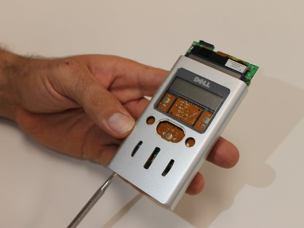 Image 1/3: Use the metal spudger to remove the device's center toggle button.