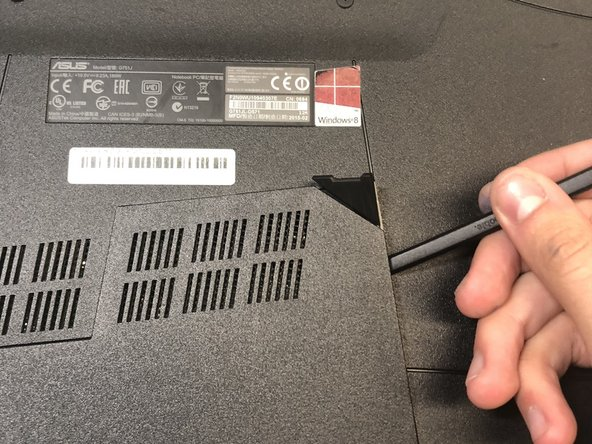Use the black nylon spudger to pry the back panel off the laptop.