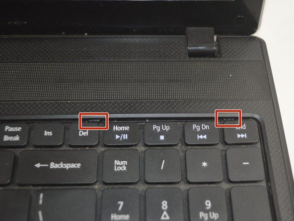 Use a spudger to push in two of the clips directly above the top row of keyboard keys.