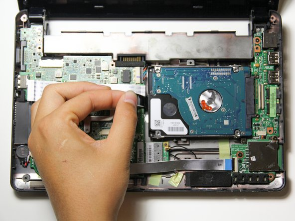 Slightly lift up the hard drive using the black tab attached to the left side of the hard drive.