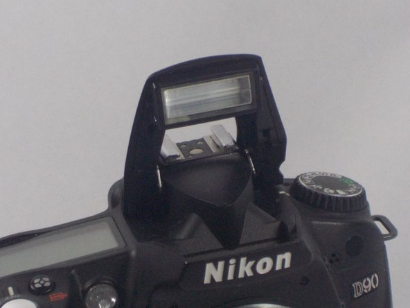 Use a plastic opening tool to lift up the flash.