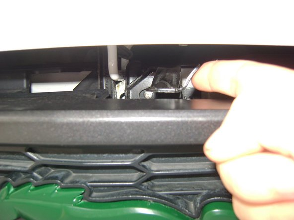 Push the latch under the center of the car's hood.
