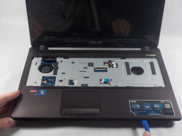 Separate the front plate of the laptop from the back using the plastic opening tool.