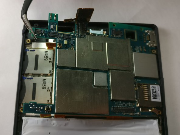 Using tweezers, carefully remove the motherboard by pulling it up and out of the backing.