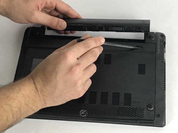 While holding the slider, pull out the old battery.