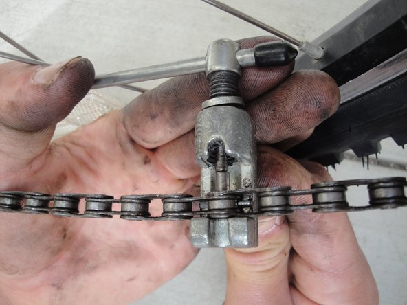 Use the chain cutter tool to press the chain pin back through the chain link. If it is difficult to push it back in, the links are not aligned properly. Realign and try again if this is the case.