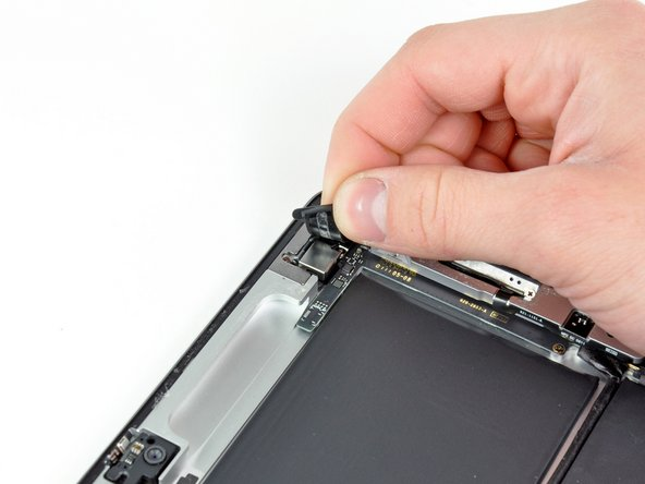 Image 1/1: Carefully peel the rubber cover off the metal camera retainer and remove it from the iPad 2.
