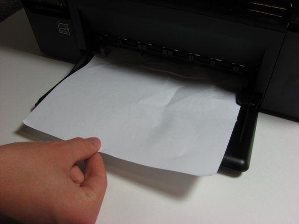 Use your hand to remove the jammed piece of paper. Pull until the paper is out.