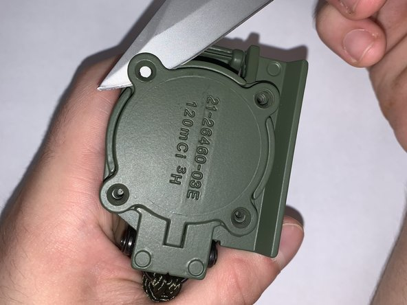 Use the pocket knife or any flat edge to pop the bottom plate out of the compass.