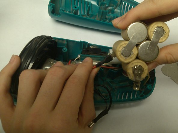 While pressure is being applied to the lock, pull the red wire away from the battery.