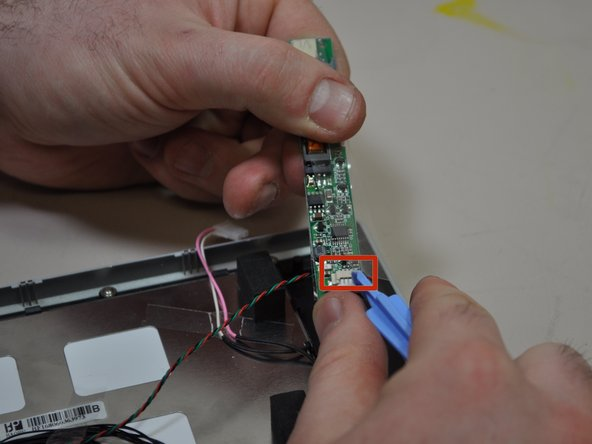 Image 1/1: Vertically flip the LCD power board so that the side that was originally facing the device is now facing up. Using your blue opening tool, remove the connection (multi-colored and twisted wire) from the Input/Output board.