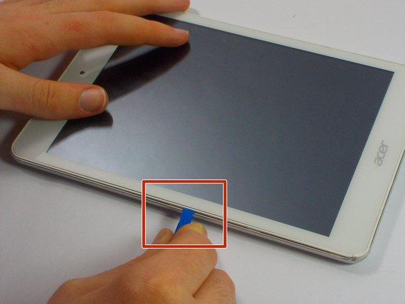 Wedge the plastic opening tool into the tiny gap between the white plastic front bezel and the aluminum rear panel.