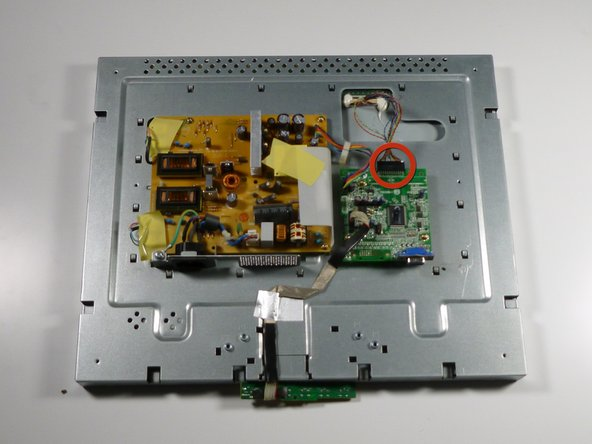 Remove the display cable located at the top of the circuit board by pulling it out towards the top of the monitor.