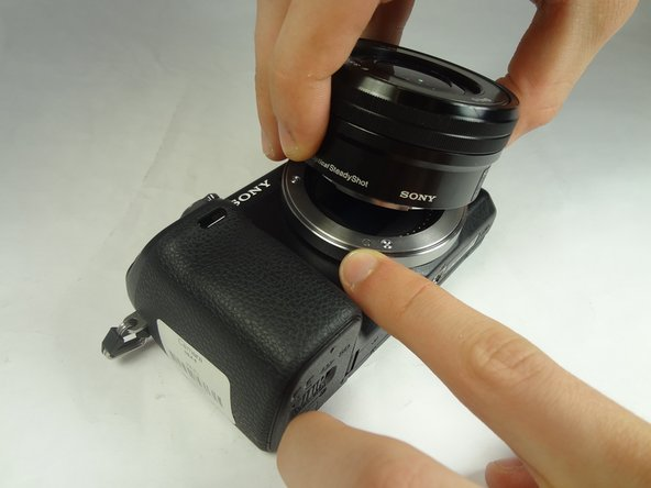 Press and hold the lens release button while rotating the lens counterclockwise.