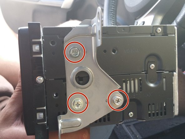 Locate the metal brackets on the side of the head unit.