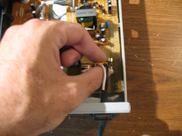 Image 1/3: Then Remove the Ribbon Cable Connector from the power supply (labeled in Black)