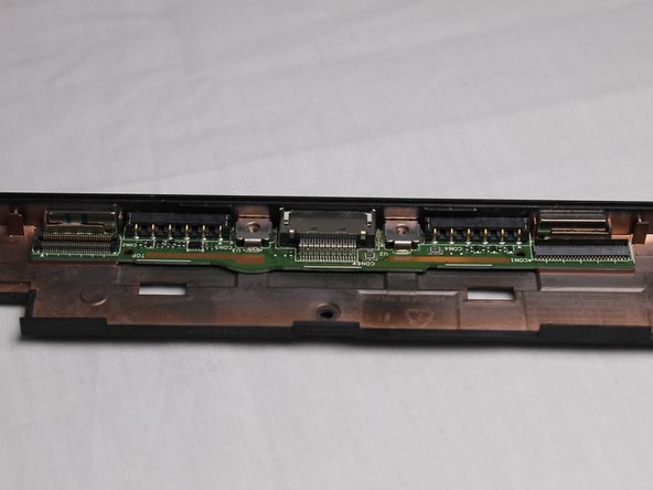 The final step is to lift the keyboard port free from the frame using your fingers.