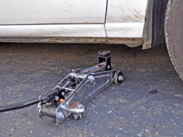 Image 2/2: Remove the jack stand and then slowly lower the jack until it is no longer supporting the car.