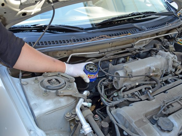 If the filter is too tight to loosen by hand, use an oil filter wrench. A wrench that fits over the top of the oil filter is ideal, as there is very little space on the sides of the oil filter. It may be necessary to access the filter from below the car if you need to use a wrench.