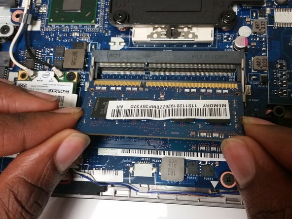 Remove the top RAM from its slot by sliding it out.