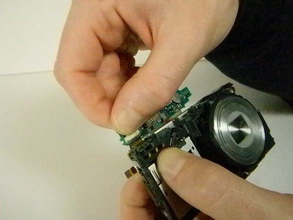Once the case is off, hold down the ribbon near the LCD screen that connects the flash to the camera. While doing this, carefully lift the control board that contains the flash until the ribbon is no longer connected.