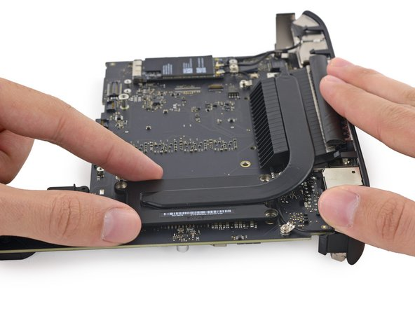 Image 1/3: If the heat sink appears to be stuck to the logic board after removing all screws, it may be helpful to use a spudger to separate the two components.