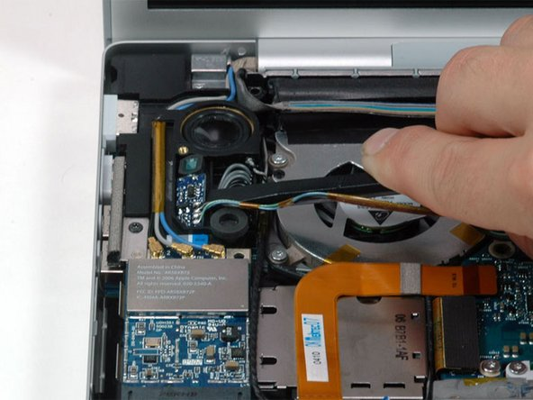 Image 1/1: Lift the left ambient light sensor board out of the computer.