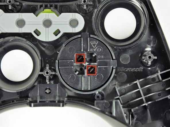 Image 1/2: Use a pair of tweezers and squeeze the clips together to release the D-pad from its backing.