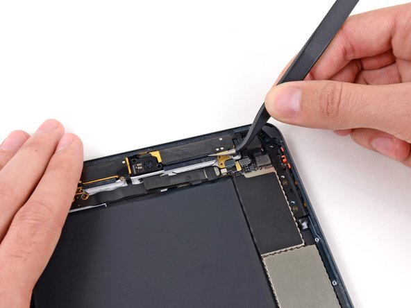 Use tweezers to lift and remove the top right antenna from the rear case.