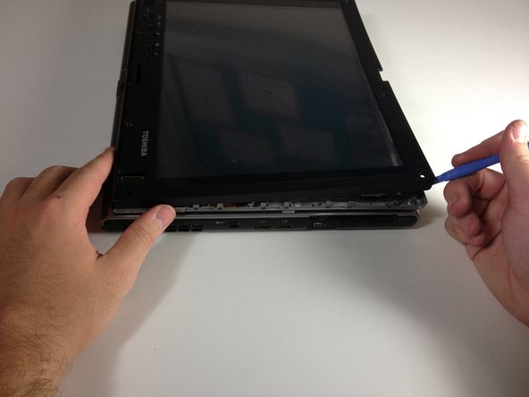 With a plastic opening tool, prop the plastic panel up to separate it from the rest of the laptop.