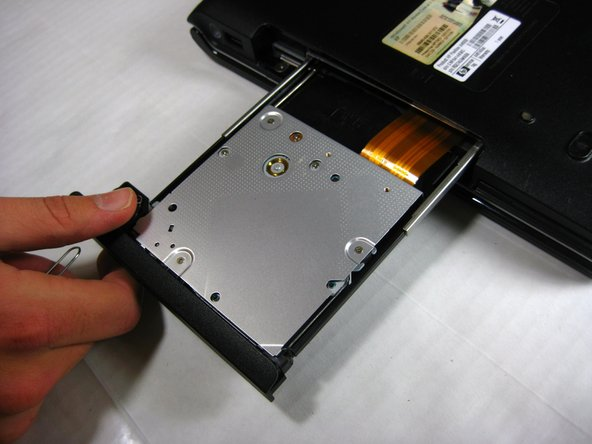 Insert the tip of an unrolled paper clip into the small hole located on the side of the optical drive.