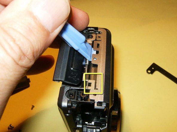 Separate the case from the catches on the sides of the camera with an opening tool.
