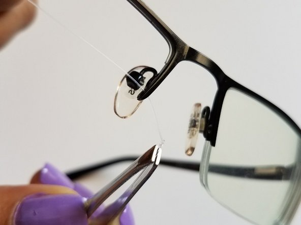 Insert one end of the wire into the hole near the pad arm and insert the other end to the opposite side of the glasses, then tie the knot as shown in the images.