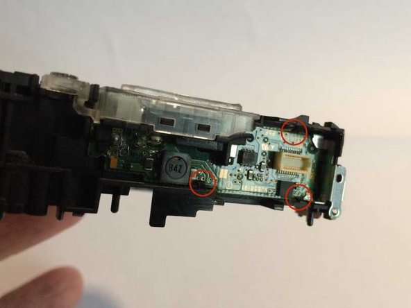 The flash assembly circuit board is retained by 3 plastic clips. Push these back just sufficiently to clear the board.