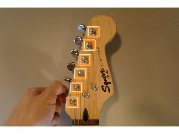 Unwind your strings by turning the tuning pegs.