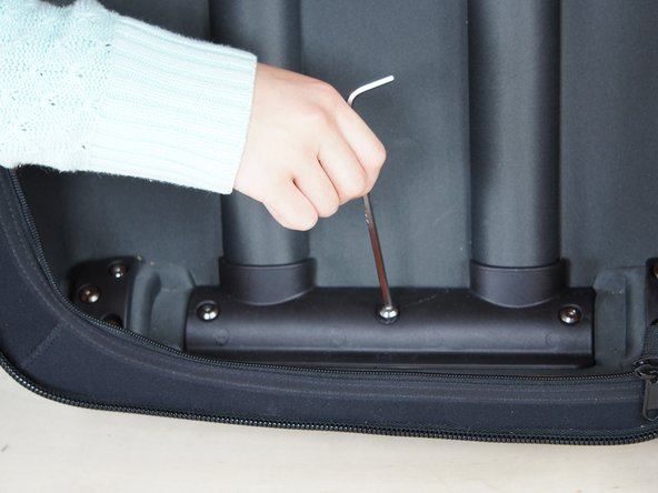 Open luggage and unzip backing, exposing back of roller. Using an Allen wrench, unscrew all 10 screws along the bottom plate and remove plastic coverings