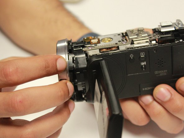 Image 1/2: Keep holding the camera with your right hand then gently remove the lens cover panel with your left hand.
