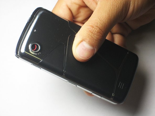Using your thumb, apply pressure to the back cover while sliding it down and off.