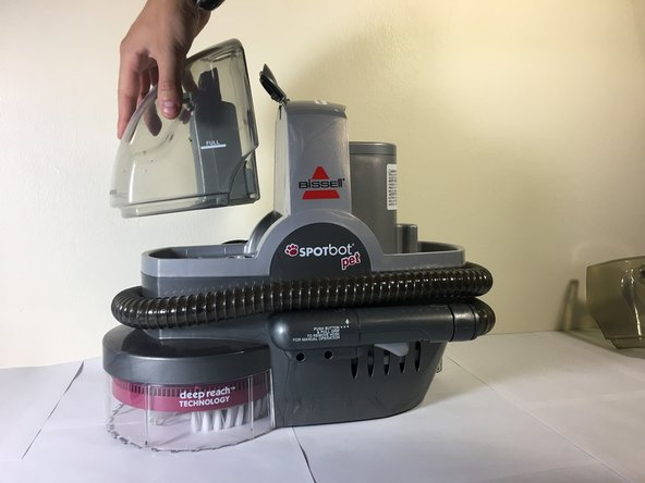 Lift up on the tab on the top of the vacuum and then lift straight up on the left container to remove it.