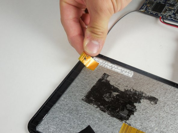 Gently peel off the orange sticker with the gray wire connected to the upper corner of the device. This is the antenna.