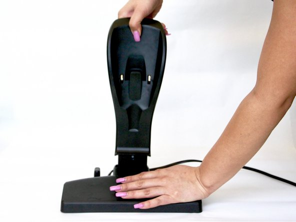 Using a firm grip, gently pull the standing charger away from the floor charger attachment