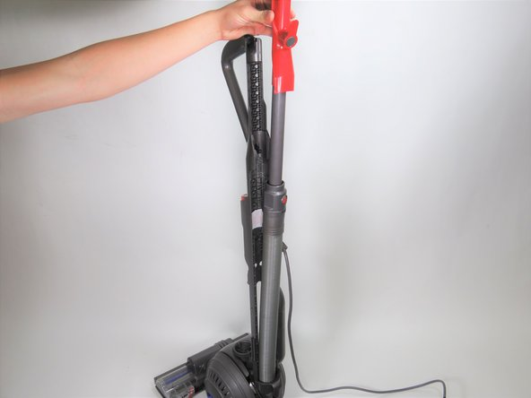 Flip the vacuum around and remove the hose so it is not blocking the back of the vacuum.