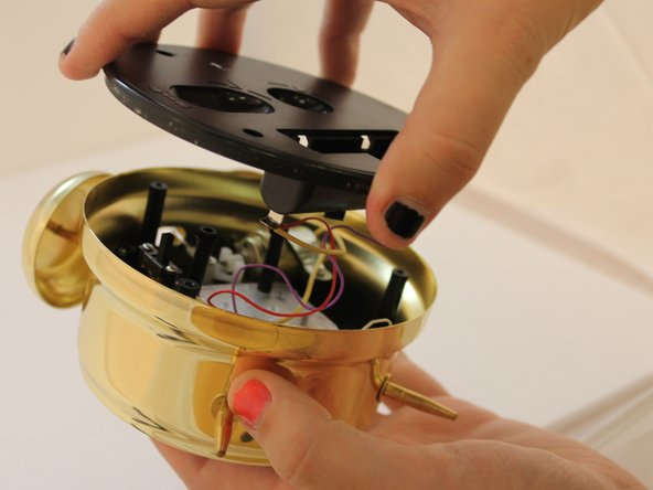 Remove the black back cover with your hand and be careful not to cut the wires attached on the cover.