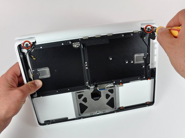 The display assembly is secured by two large T8 screws, one on each side.