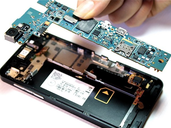 Now that all of the ribbon cables have been disconnected, carefully lift the motherboard from its housing with your thumb and index finger. Start lifting the motherboard from the bottom and work your way to the top. Hold down the phone with your other hand so you have a better grip on the device. Once removed, turn the motherboard over.